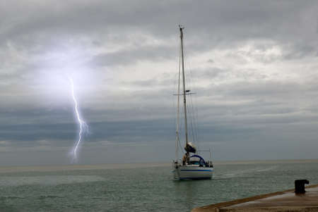 sailing near the port with lightning at horizon Stock Photo - 9897205