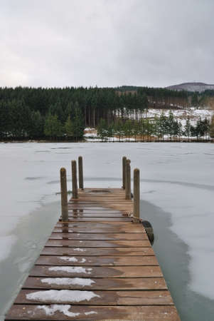 wooden pier over the frozen lake photo