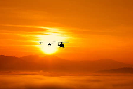 helicopter on the foggy valley at sunset