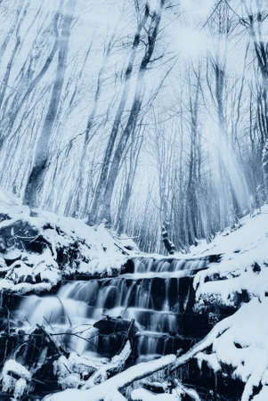 little waterfall with snow and sun beam photo
