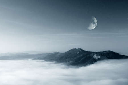 foggy hill: starry sky with moon over the foggy valley Stock Photo