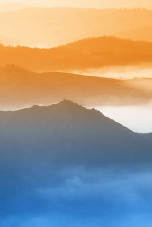 over the hill: naranja el cielo sobre el valle de niebla al atardecer