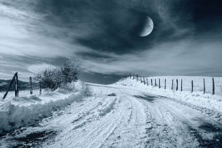 road in the night with snow and moon light photo