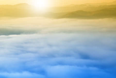 foggy hill: sun at sunrise over the clouds Stock Photo