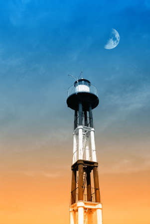 moon in the sky over the lighthouse photo