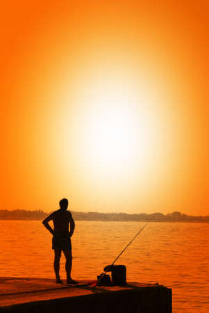 man fishing on the pier at sunset photo
