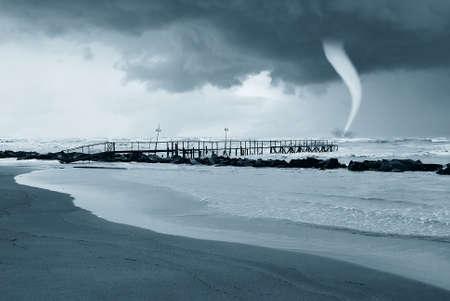 tornado over the stormy sea photo