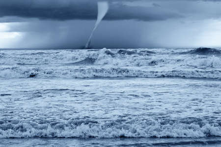 twister at horizon on the stormy sea photo
