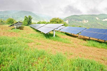 desarrollo sustentable: paneles solares en las montañas bajo el cielo nublado Foto de archivo