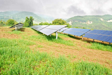sustainable development: solar panels in mountain under cloudy sky