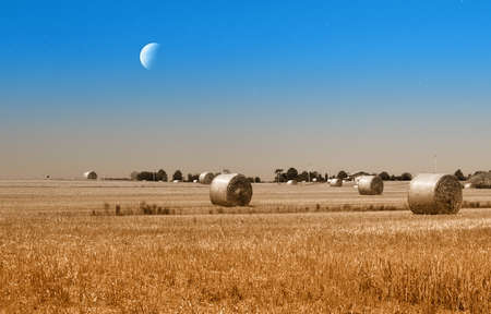 moon and stars over bales of hay in countryside photo