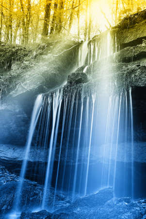 sunbeam over the waterfall in the forest photo