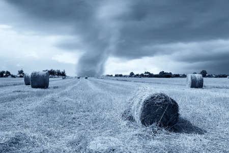 tornado at horizon over field with round bales of hay photo