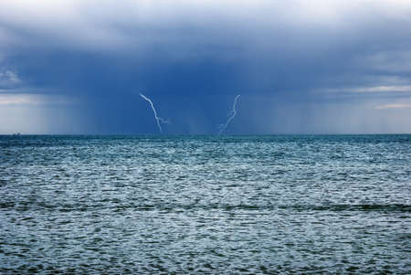 storm with lightnings over the ocean photo