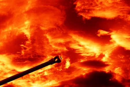 under fire: arma bajo un cielo nublado rojo fuego