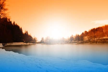orange sky over frozen lake in the evening photo