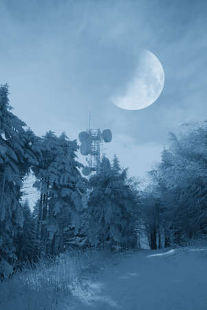 antennas for telecommunications and moon in the sky in winter photo
