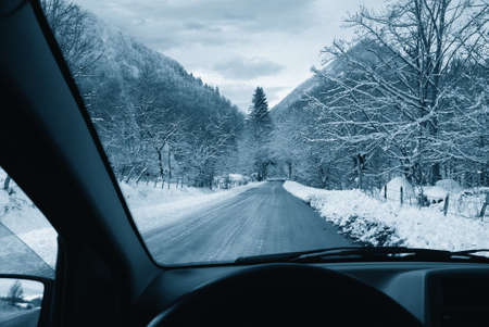 driving on snowy road in the natural park photo