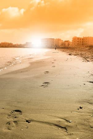 footprint near the shoreline at sunset photo