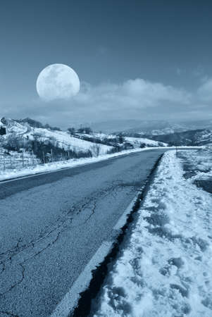 mountain road in the evening with moon in the sky photo