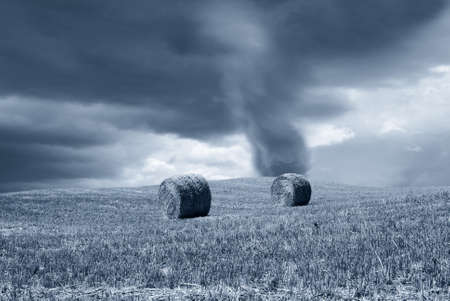 tornado in the country with round bales photo