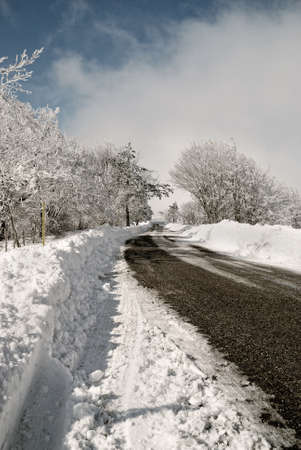 road in the snow with cloudy sky photo