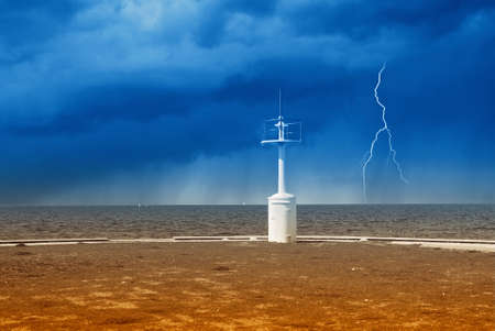 small lighthouse with storm at horizon photo
