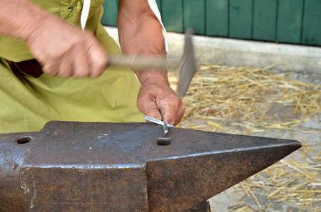 forgeman: blacksmith  creates a metal cross by hand Stock Photo