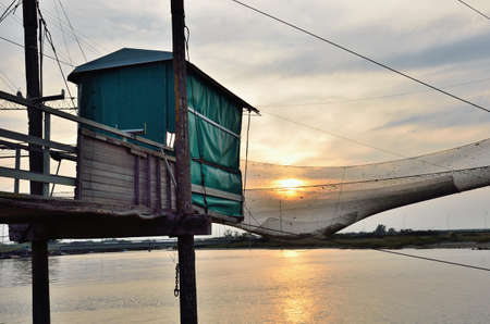 fishing hut: fishing hut over the river at sunset