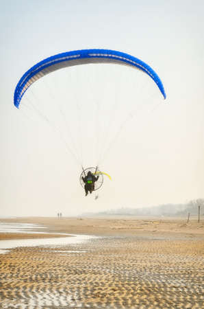 paraglider: paraglider in flight in blue sky over the beach Stock Photo