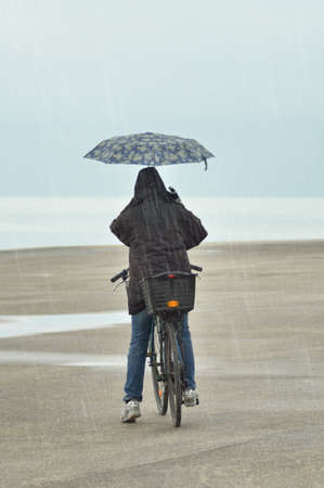 people with umbrella and bike photo