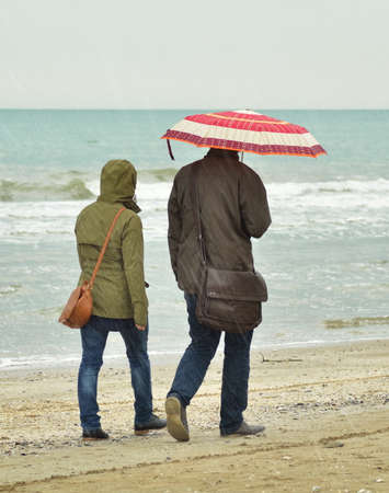 sotto la pioggia: coppia con ombrello sotto la pioggia sul litorale