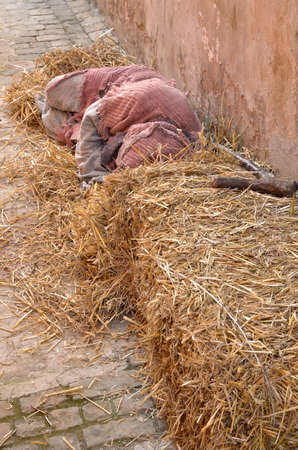 beggar: beggar in the ground with straw bales Stock Photo