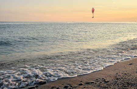 paraglider: paraglider in flight over the sea at sunset