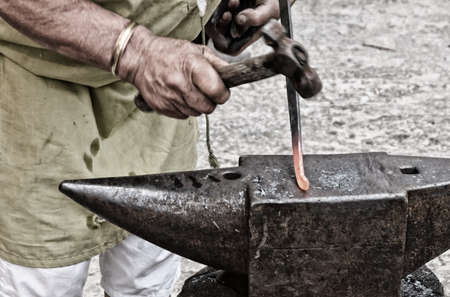 forgeman: Blacksmith at work in the workshop in Italy