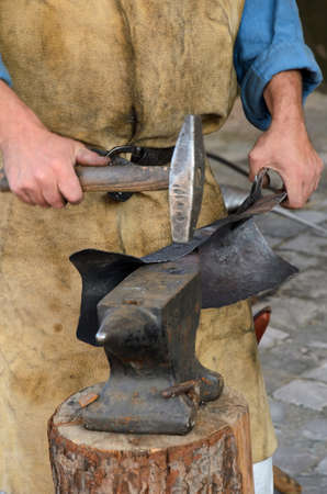 forgeman: blacksmith at work in the repair shop in italy