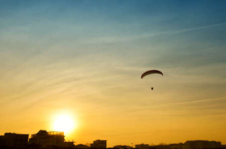 paraglider: Paraglider in flight over the town at sunset
