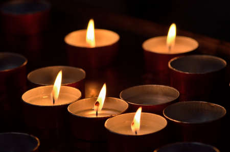 reflection of life: many lit candles in the church in Italy
