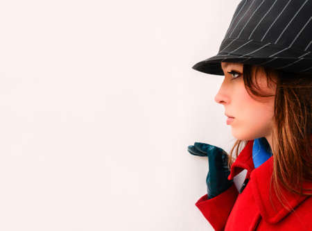 upper half: Yong woman in red coat and black hat on one side of the white wall Stock Photo