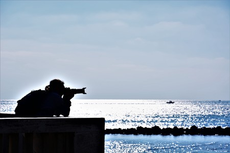 at pontile di ostia a man is taking photos of the sea with a tele lens