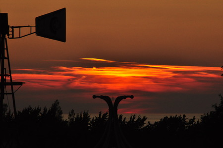 Red and orange sky with clouds and silhouettes and contrasts of objects in front