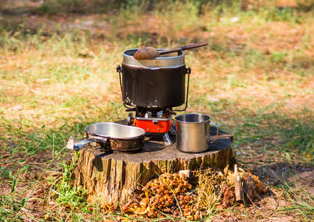 soup kettle: Marching army pot with a cup on a stump Stock Photo