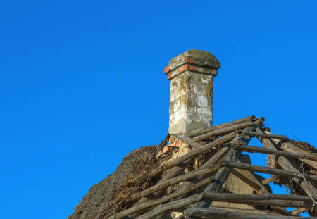 damaged roof: an old chimney in an old house with a damaged roof