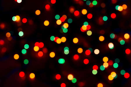Colorful beautiful multi-colored Christmas lights on a black background Stock Photo