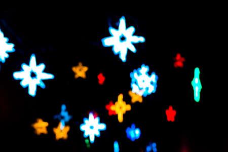 background red: hermosas estrellas de desenfoque de Navidad multicolores luces de colores sobre un fondo negro