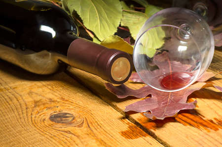 carpet stain: Red wine spilled from a glass on a wooden table on which the leaves and bottle Stock Photo