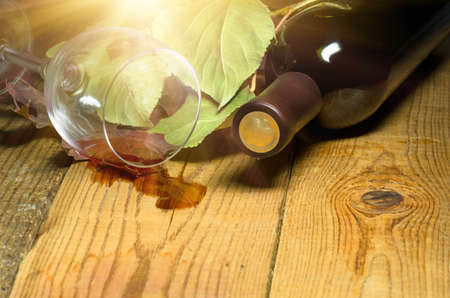 emptied: Red wine spilled from a glass on a wooden table on which the leaves and bottle Stock Photo