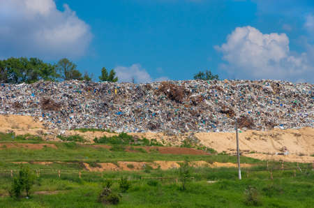 dump yard: On landfill metal mountain, plastic and rubber is ready for recycling on a background of blue sky