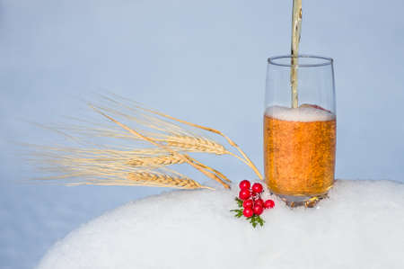 light beer in the snow with ears of wheat. winter background