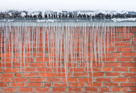 sharp: Icicles hanging against a background of red brick wall Stock Photo